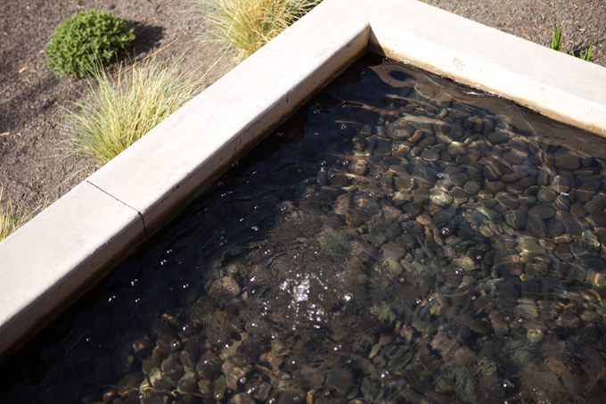 A water feature lined with river rock runs through the home's courtyard.