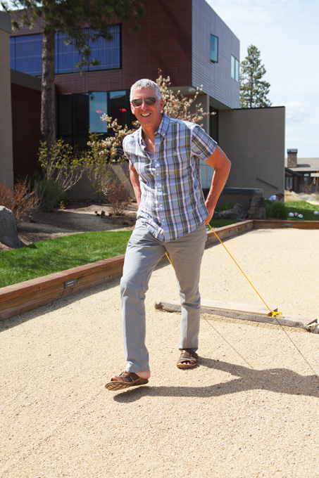 Keith Kenneally rakes the bocce ball court in preparation for a game.