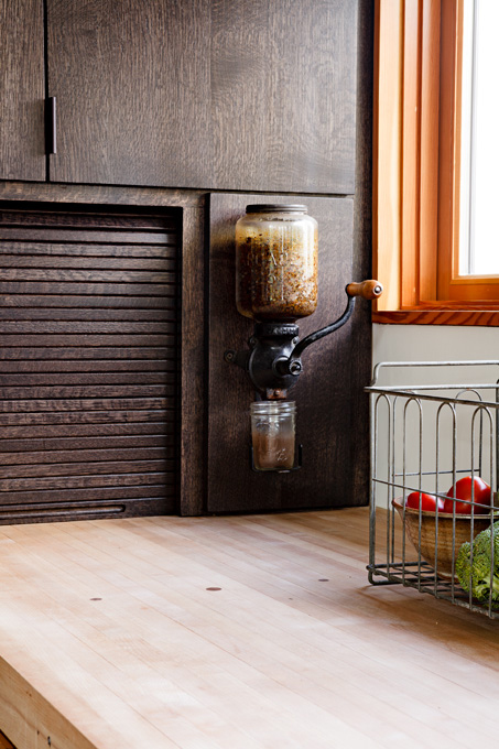 Countertops were made from old bowling alley wood; a coffee grinder is conveniently placed.