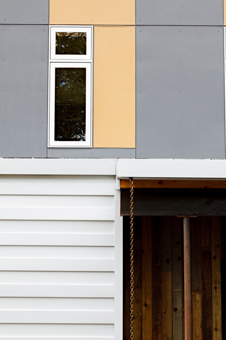 The fiber cement panels were installed wrong-side out; the corrugated metal siding is meant to last for 50 years.