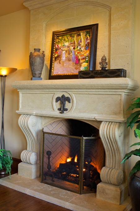 The fireplace damper is part of the French fleur-de-lis design in the mantel.